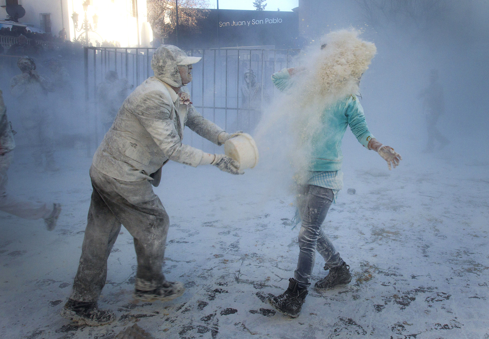 "A military dressed man throws flour at a woman's face as they take part in the battle of ""Enfarinats"", a floor fight in the town of Ibi, in the south-eastern Spain on December 28, 2012. For 200 years Ibi's citizens annually celebrate with a battle using flour, eggs and firecrackers outside the city townhall. AFP PHOTO/ JAIME REINA"